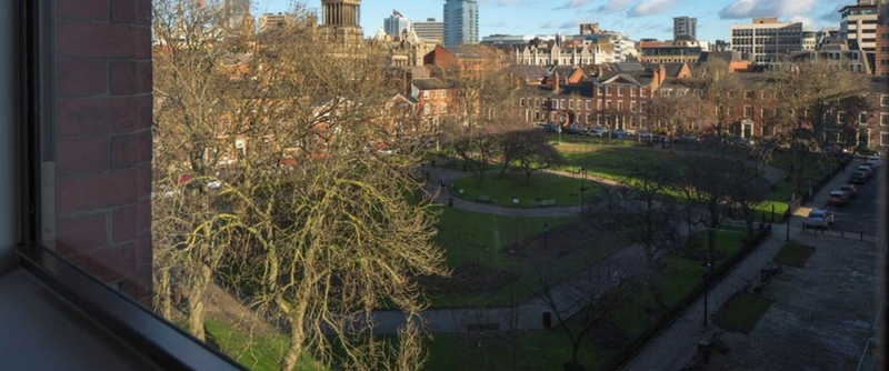 A view from a window of Leeds skyline and a quiet park.